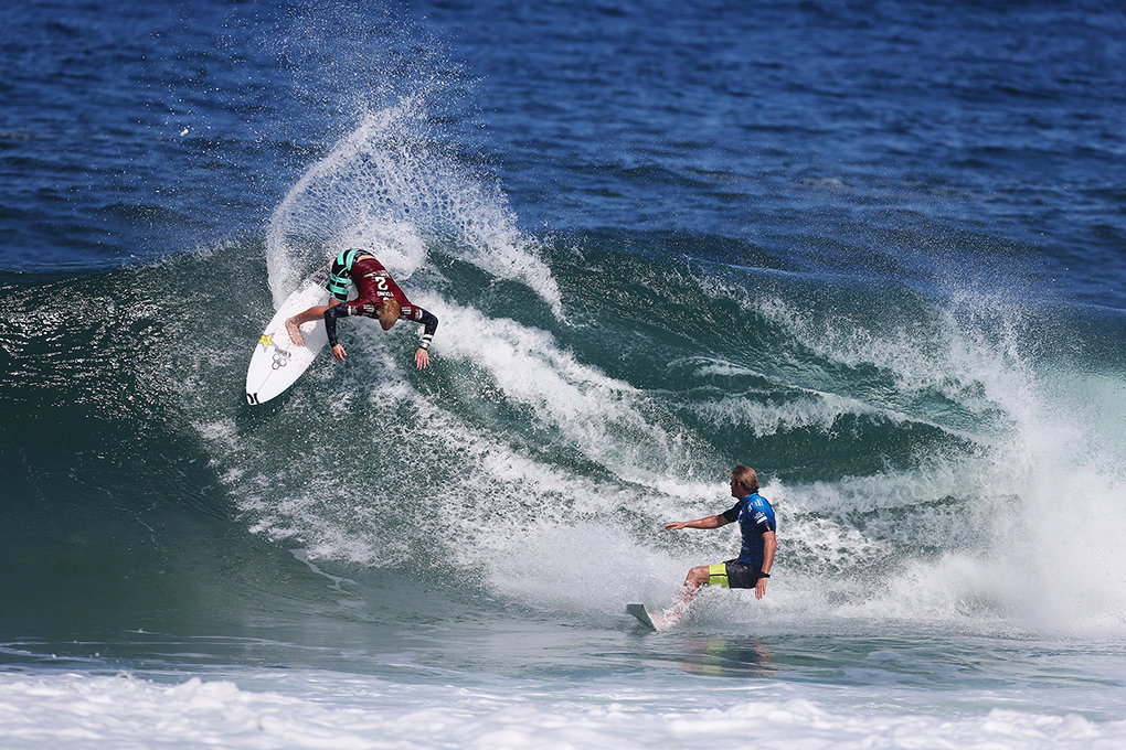 Nat Young of USA (pictured red) performs a backhand re-entry as his opponent Bede Durbidge of Australia (pictured blue) looks on during Round 1 of the Oi Rio Pro in Barra De Tijuca, Rio, Brasil on May 12, 2015. Young was penalised for interfering on Durbidge's wave and was relegated to third place while Durbidge advanced in first.